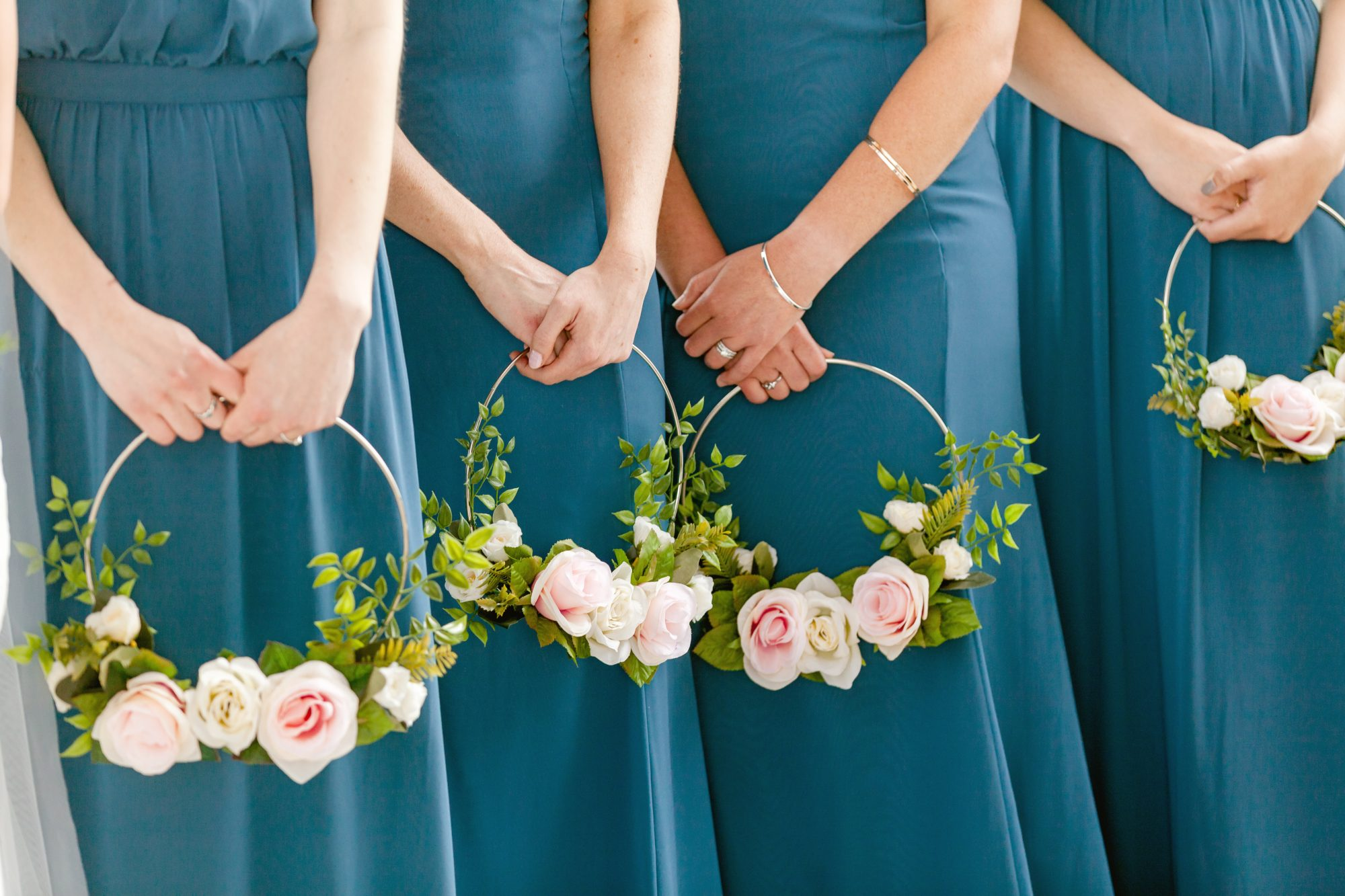 bridesmaids carrying floral wreaths